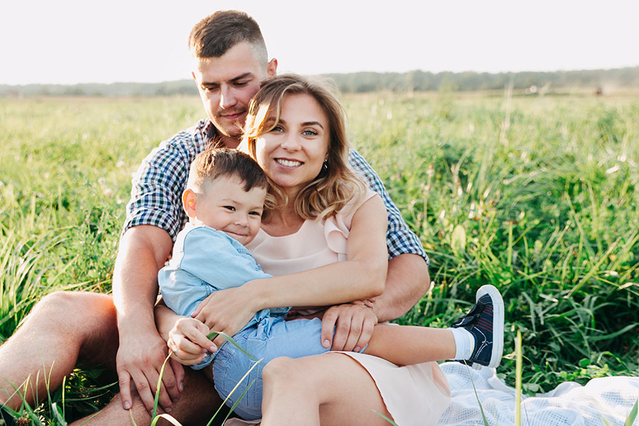 Personal Insurance - Family Hugging and Smiling in Green Grassy Field